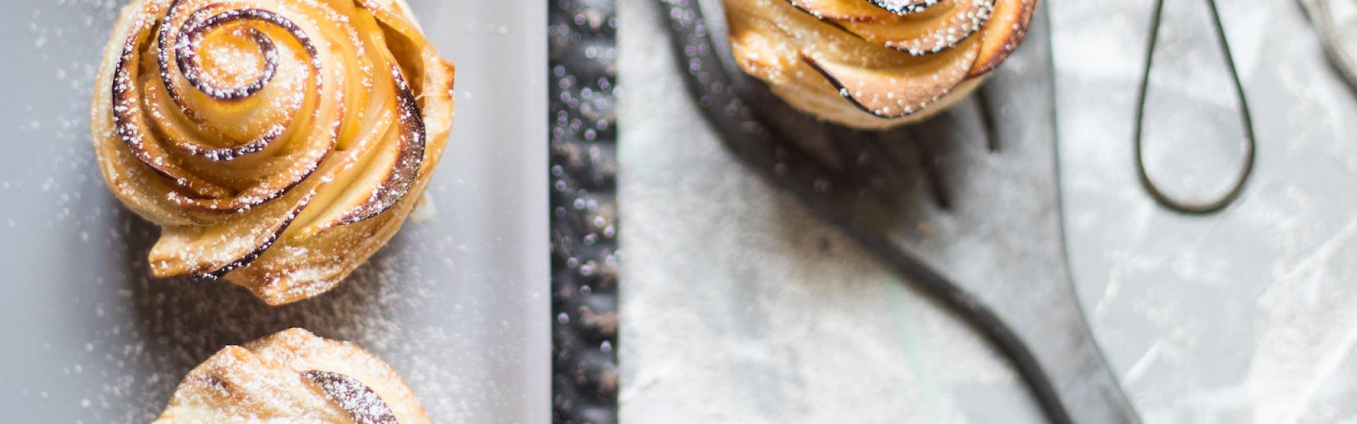 Mehrere Apfelrosenmuffin auf einem gedeckten Kaffeetisch angerichtet.