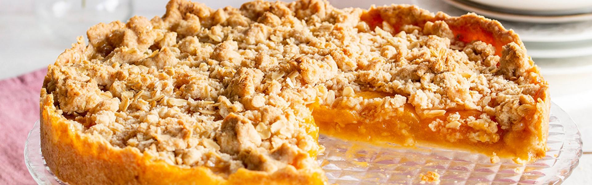 Der Aprikosenkuchen mit Streuseln steht angeschnitten auf einem Kuchentisch.