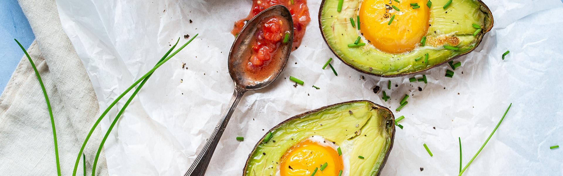 Mehrere Hälften gebackene Avocado mit Ei auf einem Stück Backpapier.