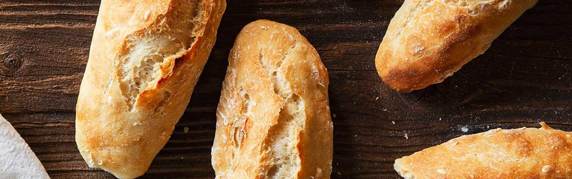 Mehrere Baguette Brötchen auf einem Holztisch.