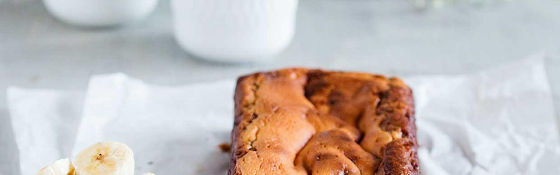 Banana Bread mit Cheesecake-Swirl liegt angeschnitten auf einem Stück Backpapier.