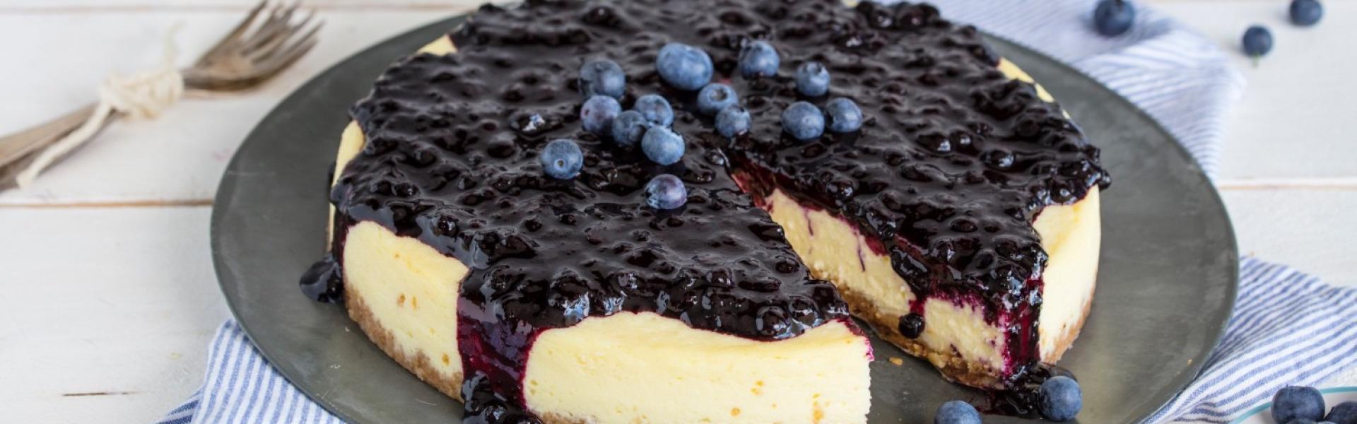 Angeschnittener Blueberry Cheesecake auf einem großen Teller serviert.