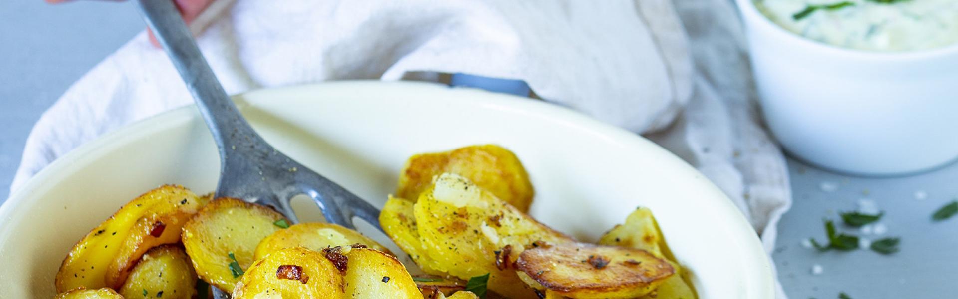 Bratkartoffeln aus gekochten Kartoffeln in einer Pfanne, die mit einem Pfannenwender herausgenommen werden.