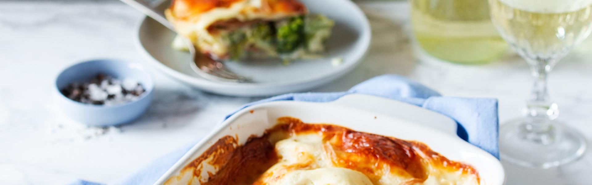 Brokkoli-Lasagne in einer Auflufform auf einem gedeckten Tisch.