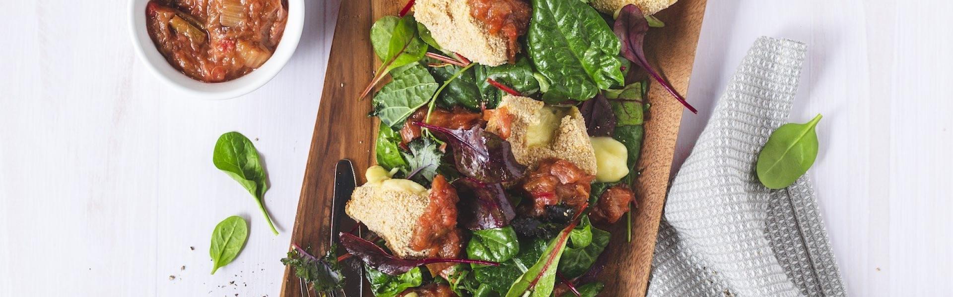 Panierter Camembert in Stücken auf Salat mit Chutney angerichtet.