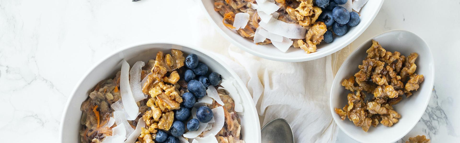 Carrot Cake Porridge mit Blaubeeren, Nüssen und Kokos in zwei Schalen.