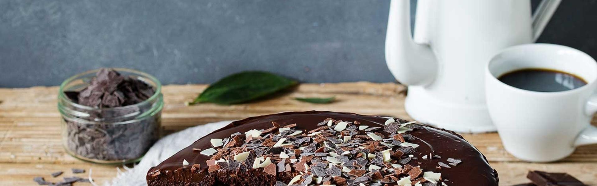 Death by Chocolate angeschnitten auf einer Kuchenplatte auf einem gedeckten Tisch.