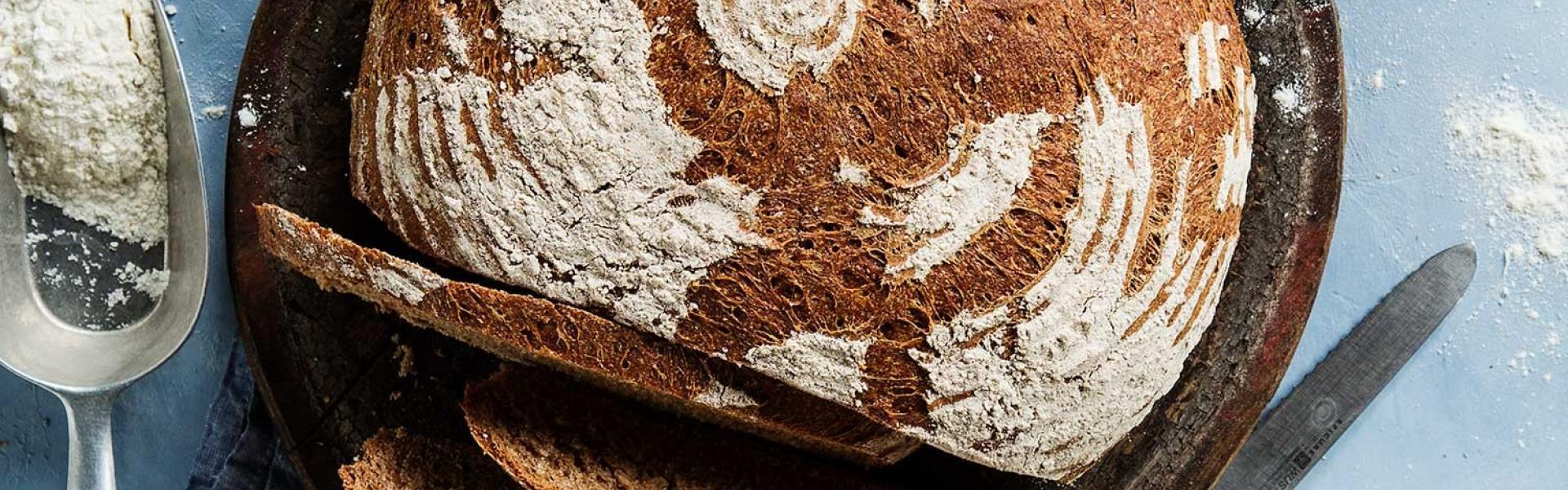Dinkelbrot angeschnitten mit Zutaten im Hintergrund.