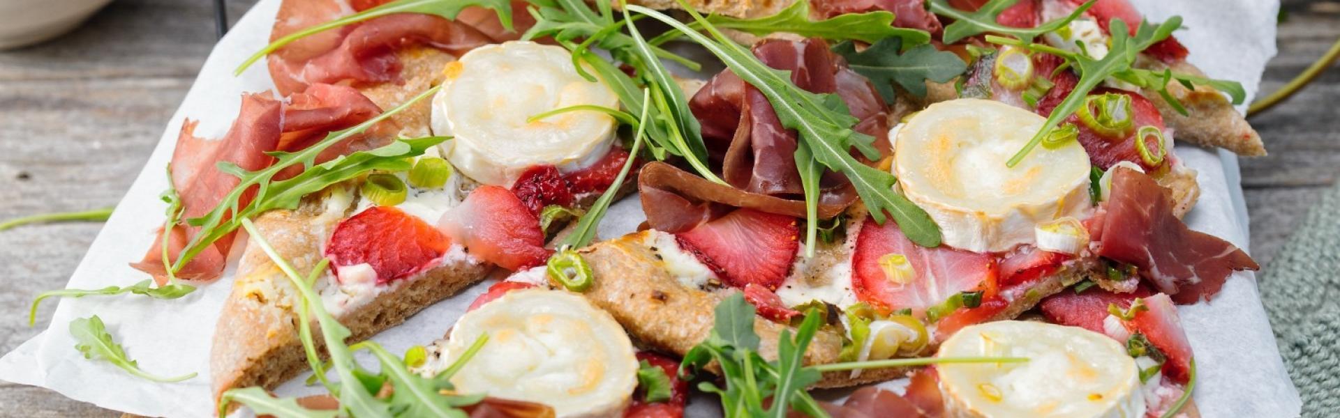 Dinkelpizza mit Erdbeeren, Ziegenkäse, Bresola und Rucola auf Holzbrett.