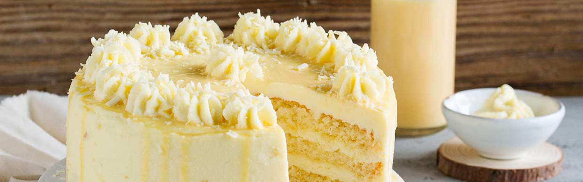 Die Eierlikör Drip Cake mit weißer Schokolade liegt angeschnitten auf einer Etagere. Drumherum ein gedeckter Kaffeetisch und ein Teller mit einem Stück davon.