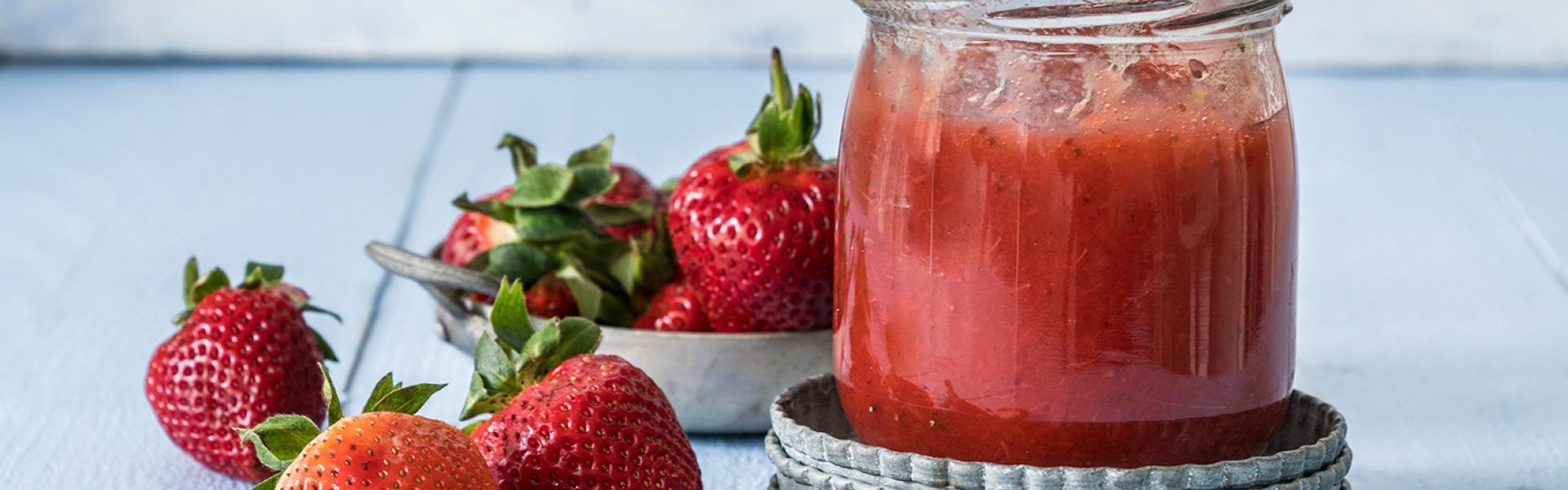 Erdbeermarmelade ohne Zucker in einem Glas mit Löffel, daneben Erdbeeren.