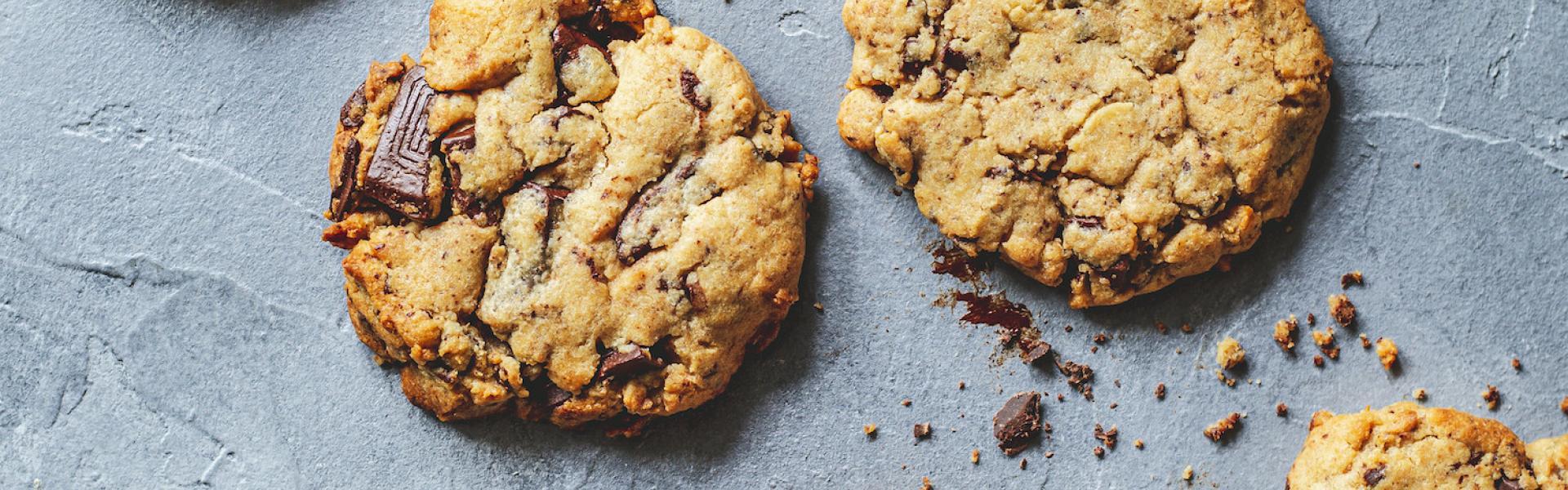 Mehrere Erdnussbutter Cookies mit Schokolade auf einem dunklen Untergrund.