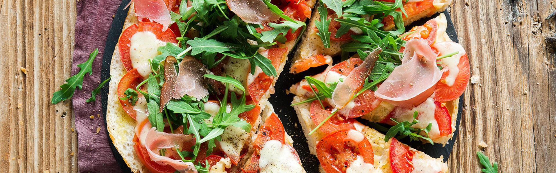 Fladenbrotpizza mit Schinken und Rucola angeschnitten auf einem Teller.