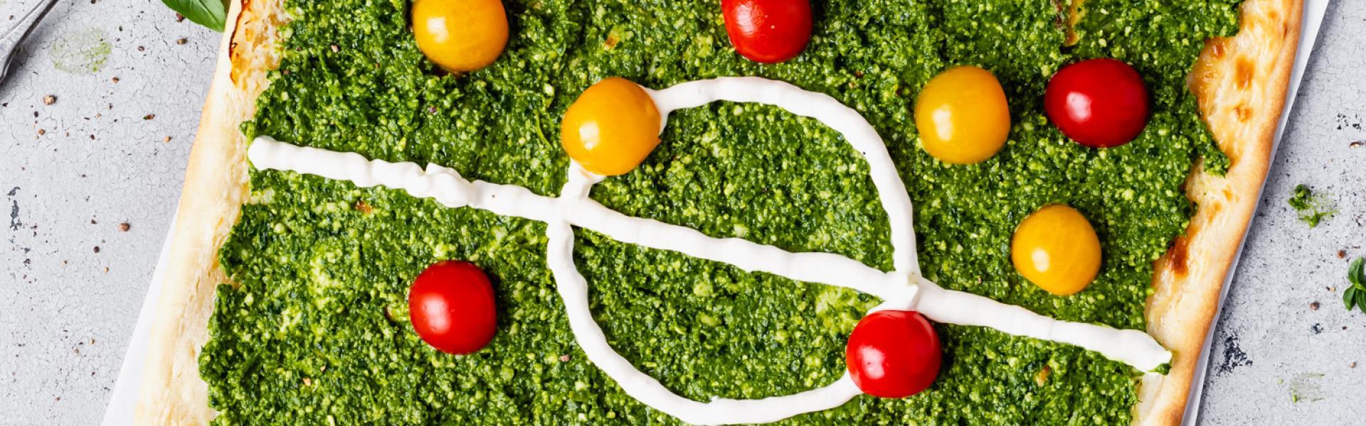 Flammkuchen mit Pesto und Tomaten, das aussieht wie ein Fußballfeld