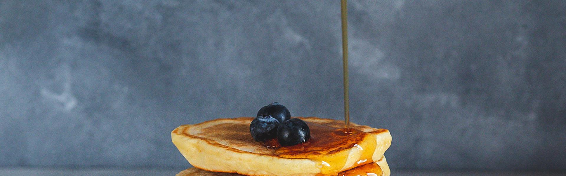 Fluffige Pancakes mit Blaubeeren auf einem Teller übereinander gestapelt und werden mit Ahornsirup übergossen.