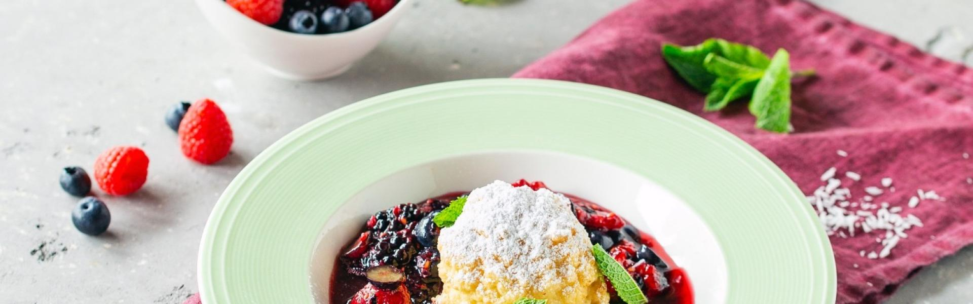 Frittiertes Eis im Kokosmantel auf Beerenspiegel in tiefem Teller.