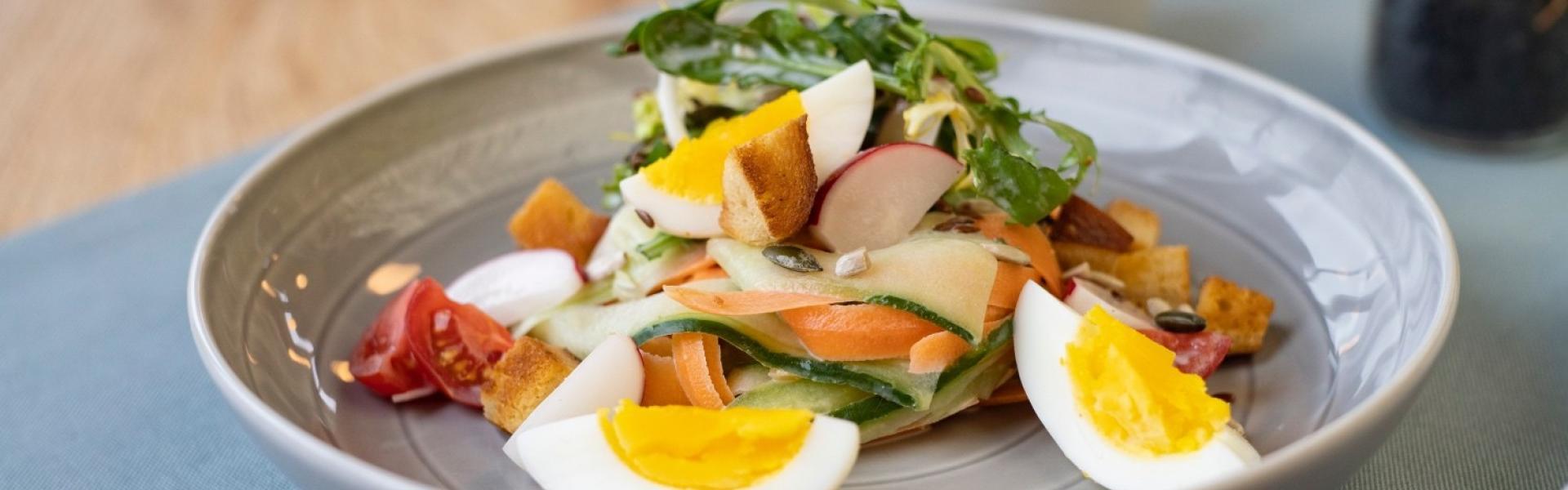 Frühlingssalat mit Ei und Croûtons auf grauem Teller