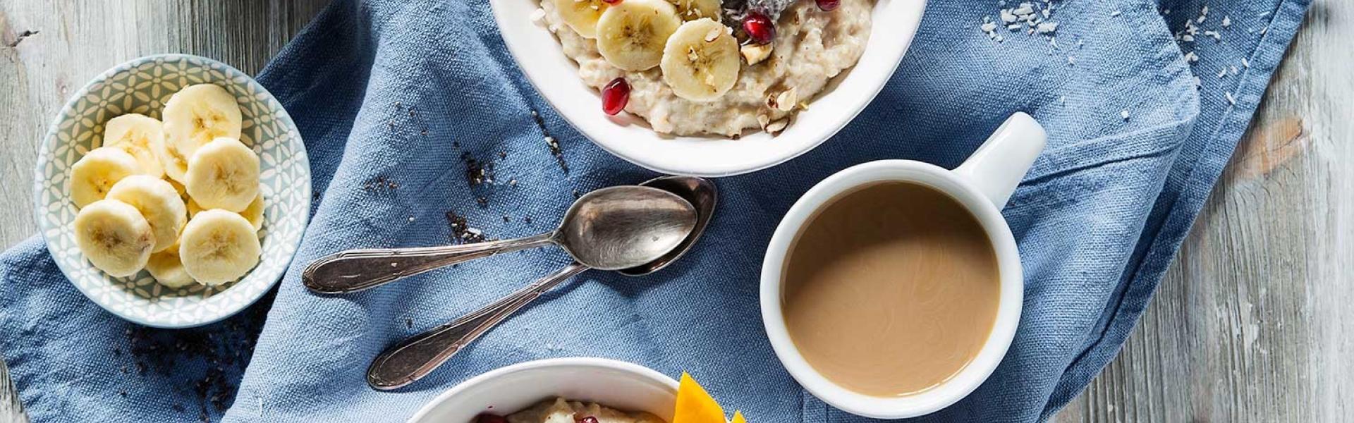 Frhstücks-Bowl auf einem Tablett mit Kaffee und weiteren Zutaten angerichtet.