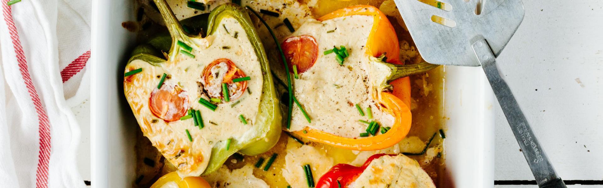 Mehrere gefüllte Paprika mit Ziegenfrischkäse in einer Auflaufform.