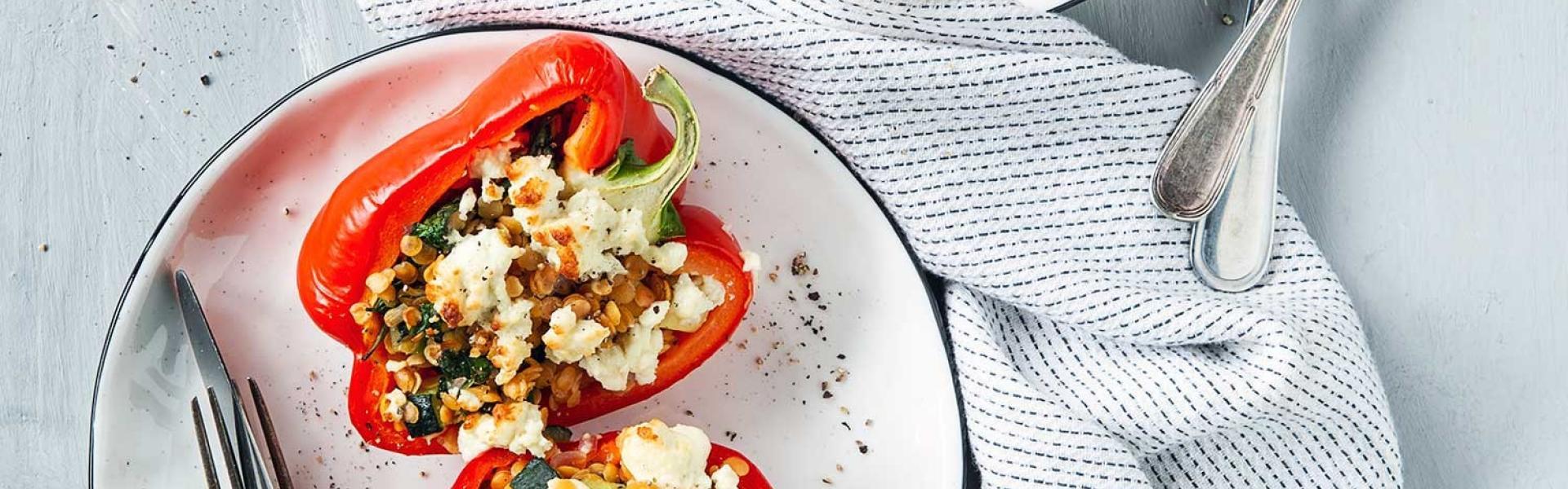 Zwei Teller mit gefüllten Paprika mit Feta und Linsen.