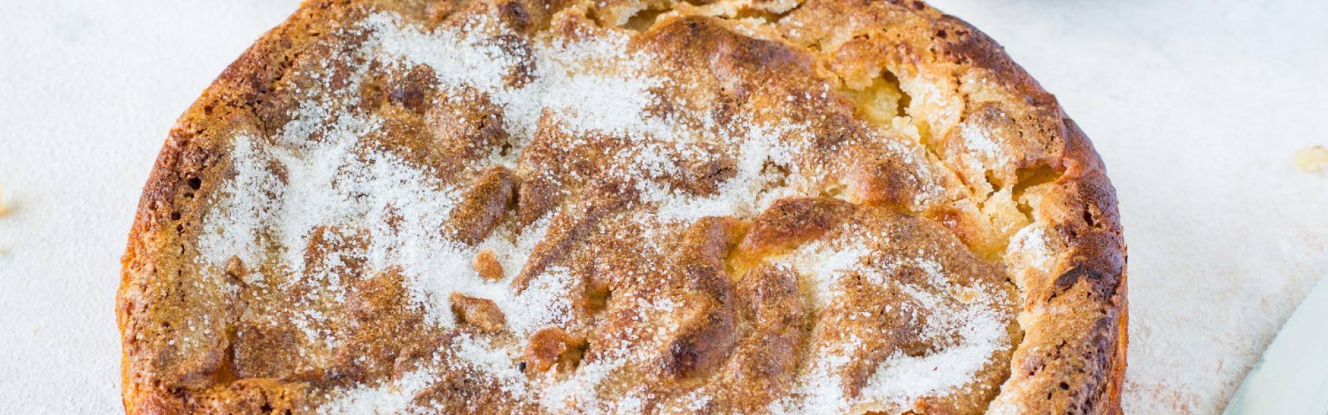 Glutenfreier Apfelkuchen mit Zuckerdecke auf weißem Tisch.