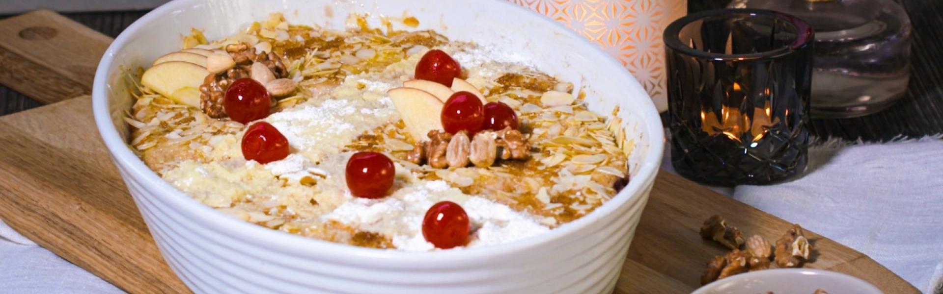 Grießauflauf in weißer Auflaufform mit Mandelkruste und Kirschen garniert.