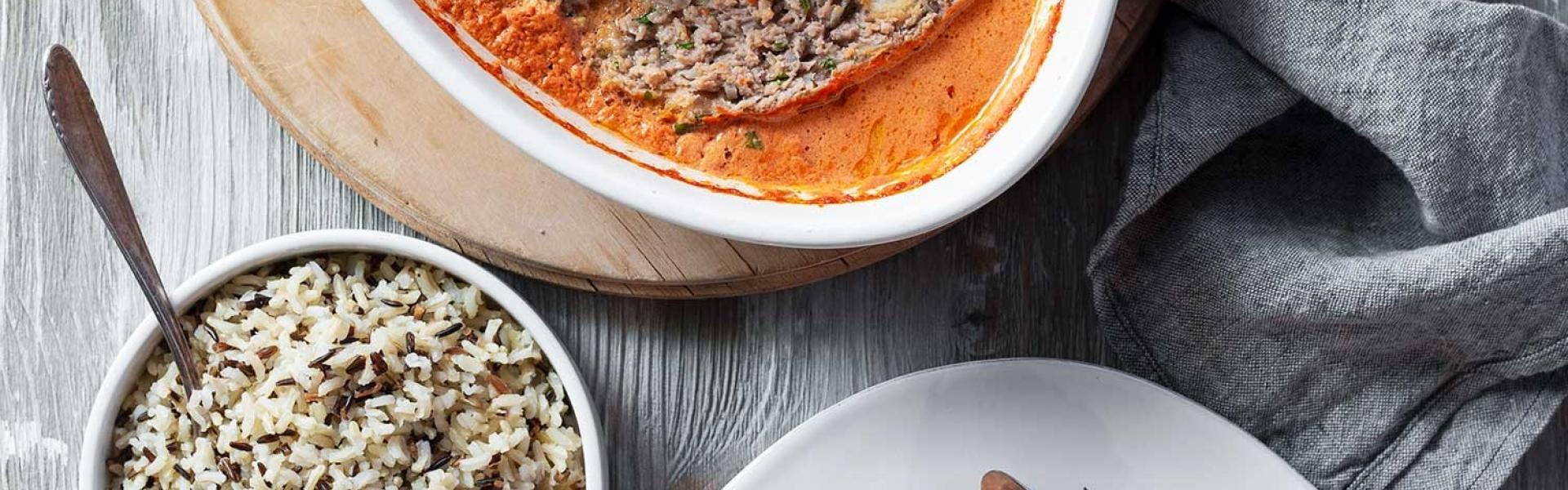 Hackbraten mit Soße in einer Auflaufform und auf einem Teller mit Reis.