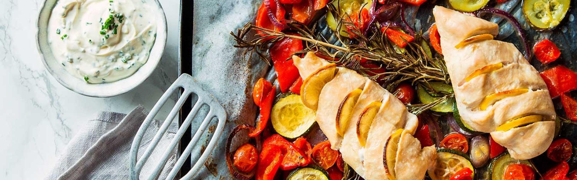 Backblech mit Gemüse und darauf Hähnchen aus dem Ofen.