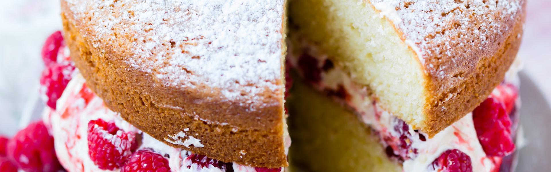 Himbeer-Biskuit-Torte angeschnitten auch einer Kuchenplatte.