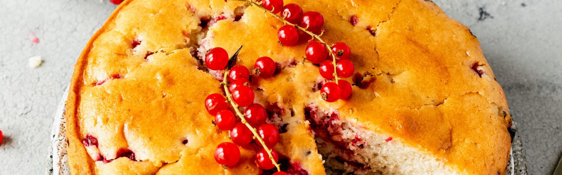 Johannisbeerkuchen vegan angeschnitten auf einer Kuchenplatte neben Johannisbeeren in einer Schale.