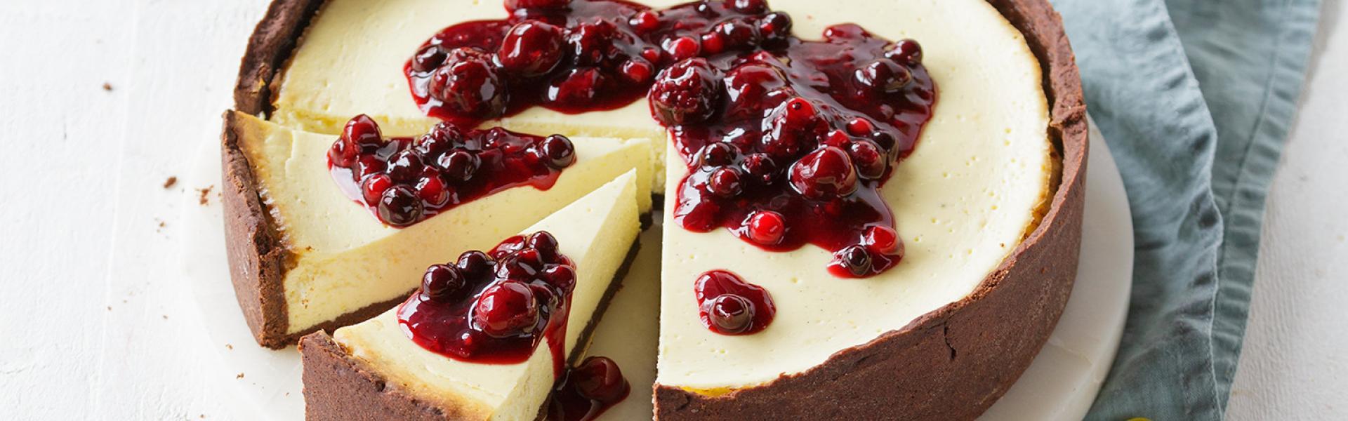 Angeschnittener Käsekuchen mit Schokoboden und Beeren-Topping auf einer Kuchenplatte.