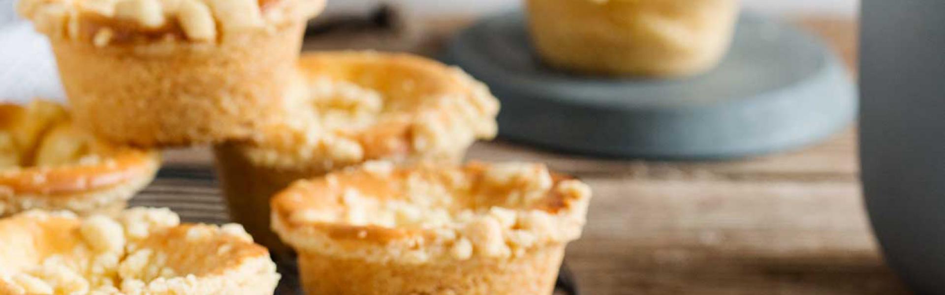 Mehrere Käsekuchemuffins mit Streuseln stehen auf einem Kuchengitter und auf einem Teller.