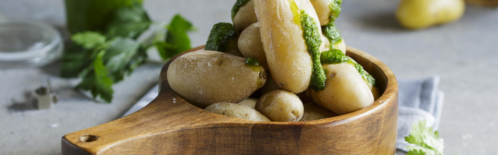 Kanarische Kartoffeln mit Mojo Verde in einer Schale auf einem Tisch.