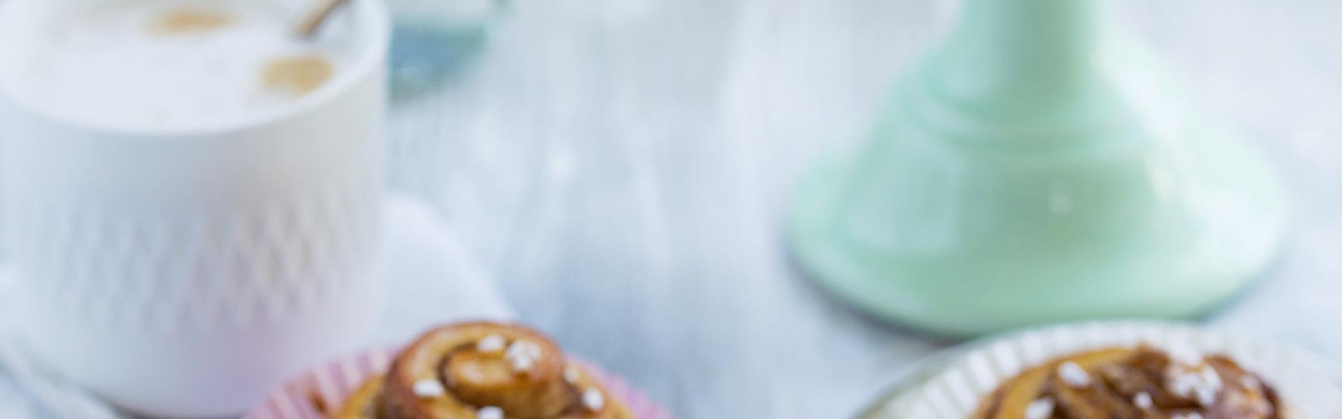 Kanelbullar auf einem Kaffeetisch und einer Etagere angerichtet.