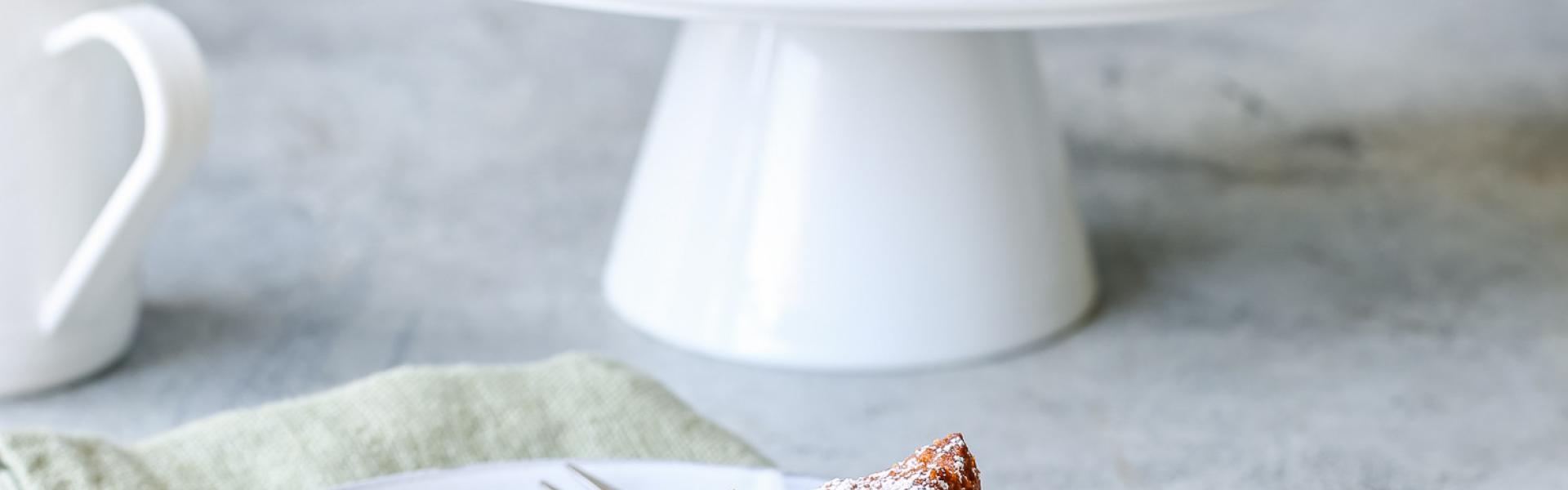 Karottenkuchen vegan angeschnitten auf einer Etagere. Davor ein Stück auf einem Teller.