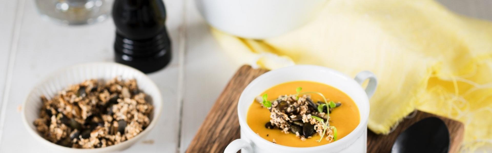 Zwei Schalen Karotten-Ingwer-Suppe auf einem Holzbrett auf einem Tisch angerichtet.
