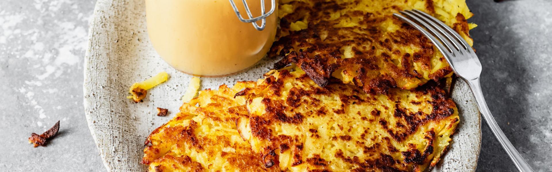 Kartoffelpuffer vegan zubereitet auf einem Teller mit Apfelmus.