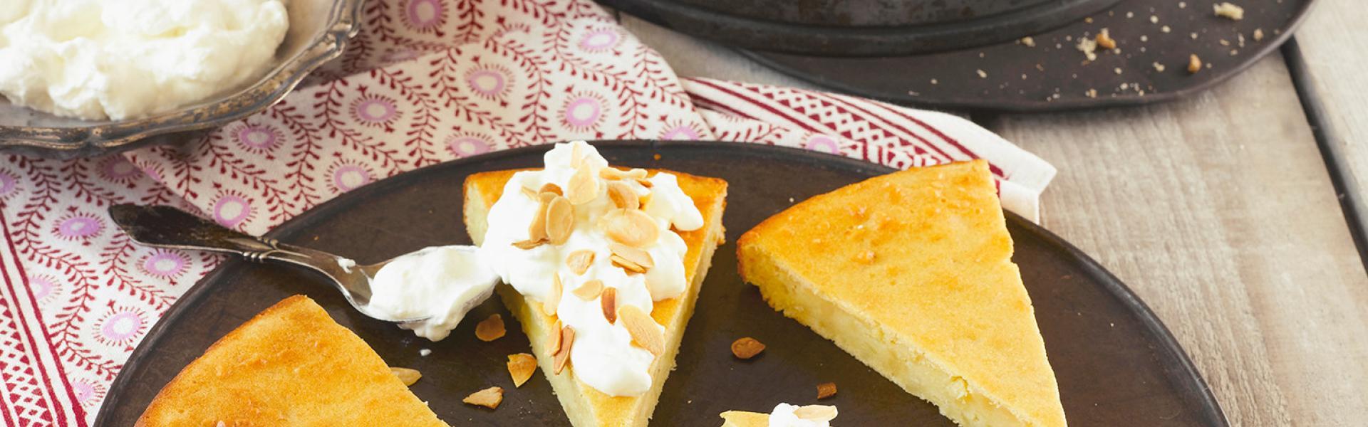 Kartoffelkuchen süß in Stücken mit Sahne und Mandelblättchen auf einem Teller.