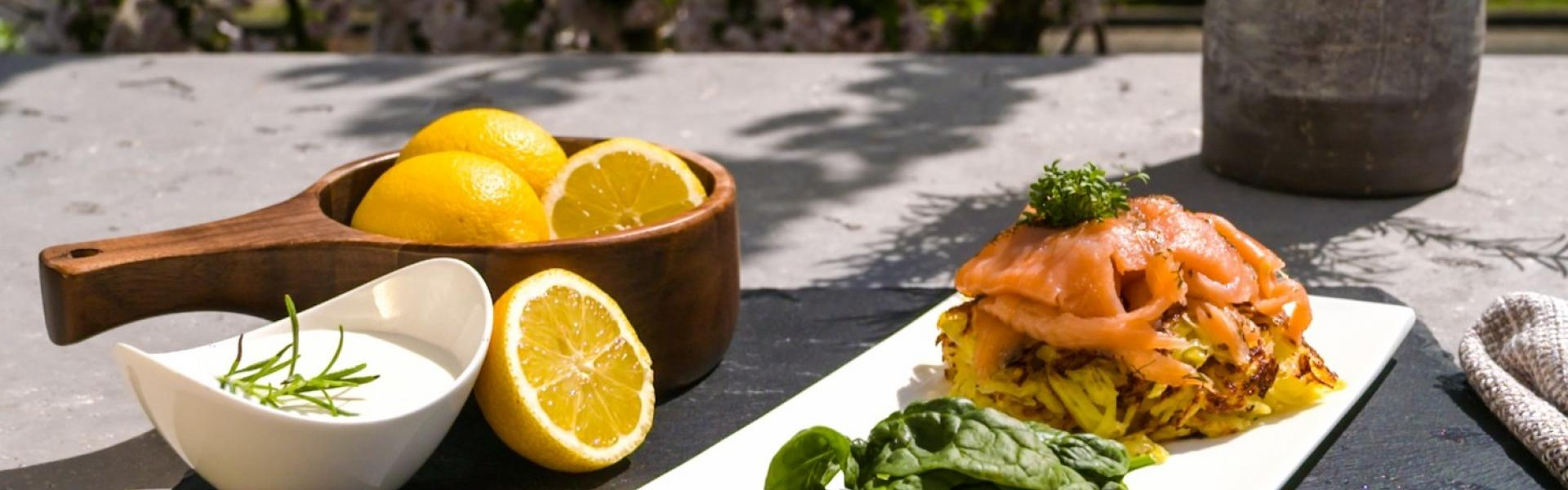 Kartoffelpuffer mit Lachs auf einem Teller angerichtet.