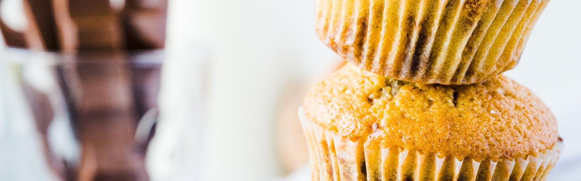 Drei Kinderschokolade-Muffins übereinandergestapelt mit Kinderschokolade im Hintergrund.