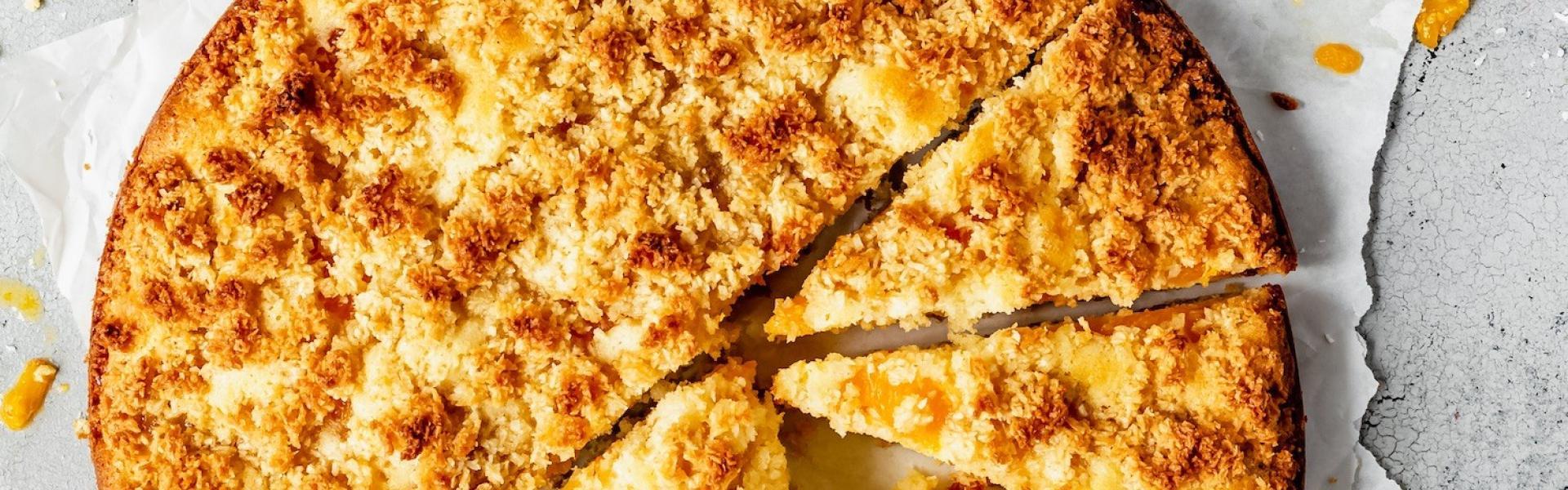 Kokos-Mandarinen-Kuchen halb in Stücke geschnitten auf etwa Papier.