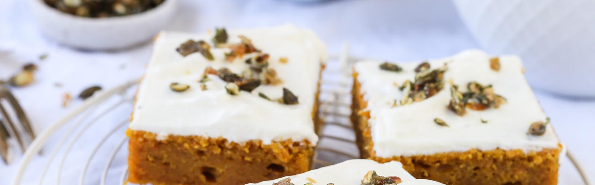 Mehrere Stücke Kürbiskuchen vom Blech mit Frosting auf einem Kuchengitter.