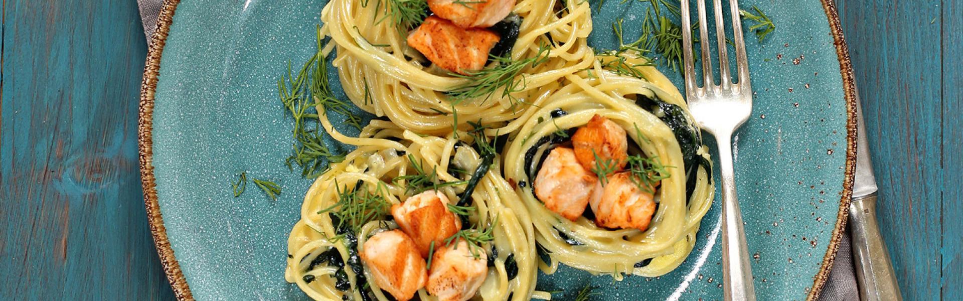 Lachs-Spaghettinester mit Gorgonzola und Spinat auf einem Teller.
