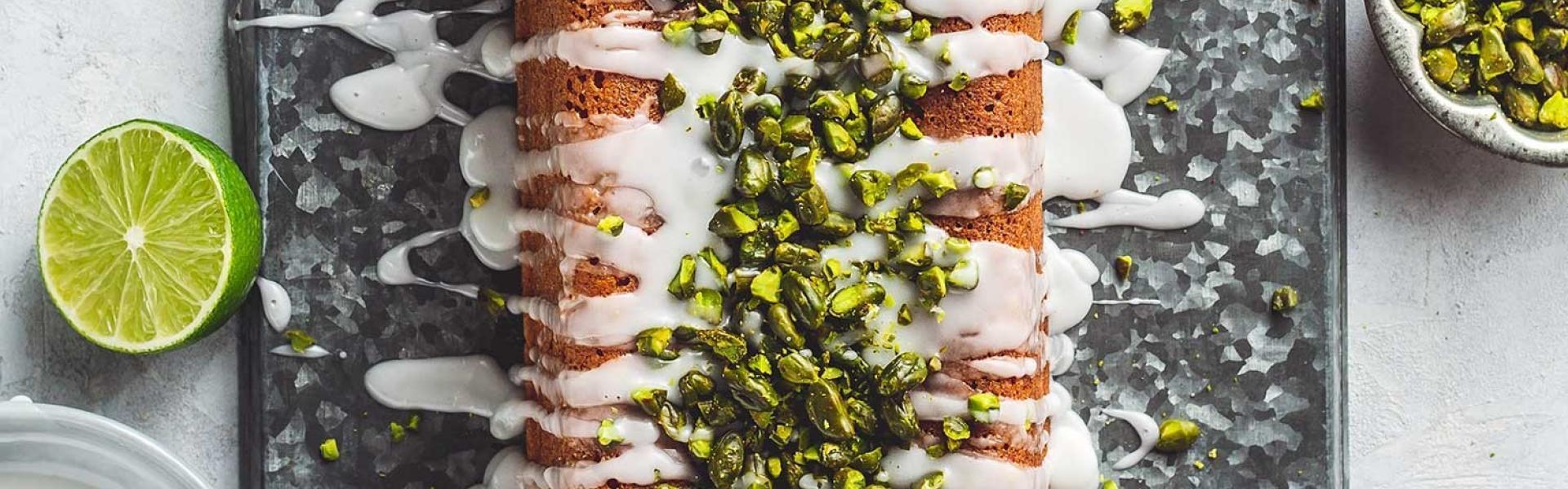 Limettenkuchen mit Zuckerguss und Pistazien angeschnitten auf einer Platte, daneben Limette, Pistazien und Guss in einer Schale.