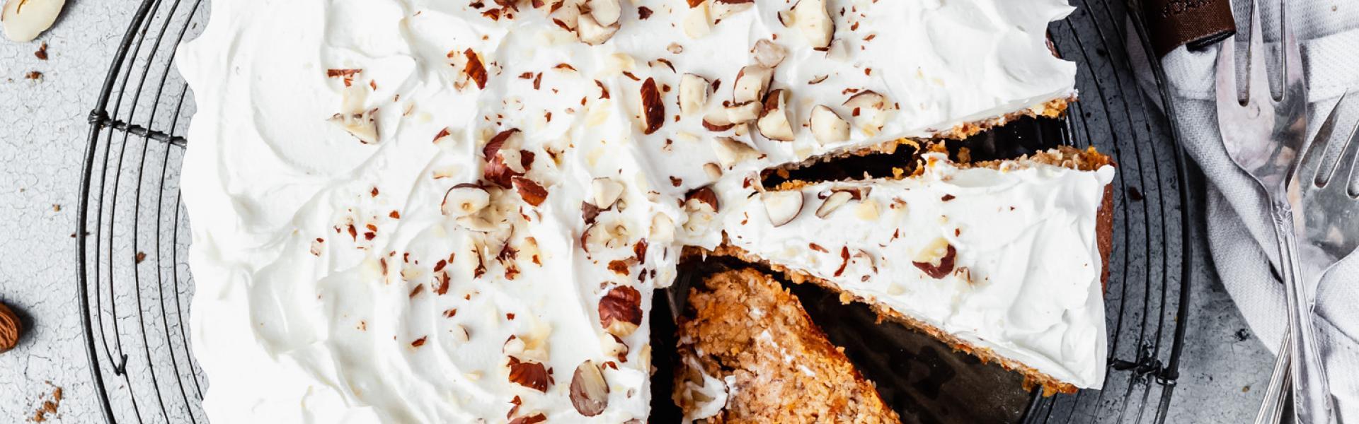 Low Carb Karottenkuchen mit Frosting angeschnitten auf einer Kuchenplatte.