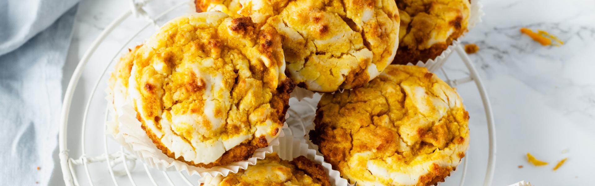 Mehrere Low Carb Kürbismuffins mit Cheesecakeswirl auf einem Tisch.