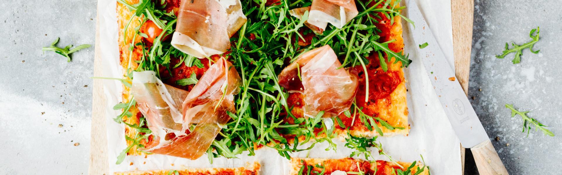 Low Carb Pizza mit Hüttenkäse auf einem Brett in Stücke geschnitten.