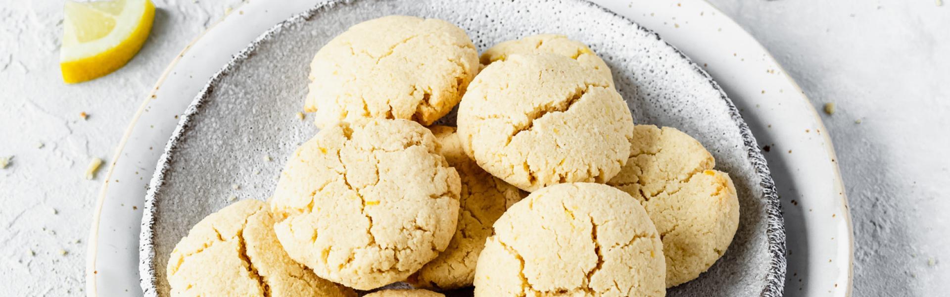 Mehrere Low Carb Zitronen-Frischkäse-Kekse auf Tellern.