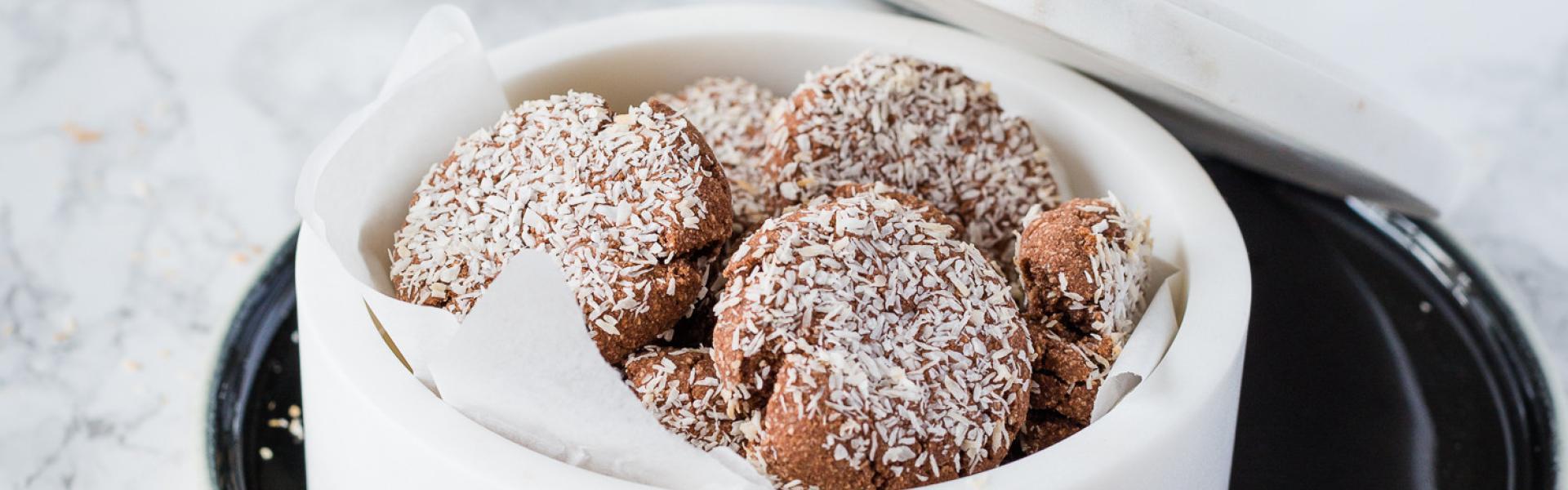 Low Carb Schoko-Kokos-Kekse in weißer Schale in weihnachtlichem Setting.