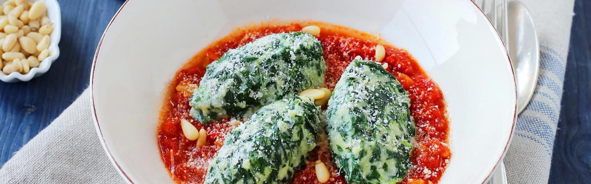 Malfatti auf Tomatensugo in einem Teller angerichtet und auf einem gedeckten Tisch.